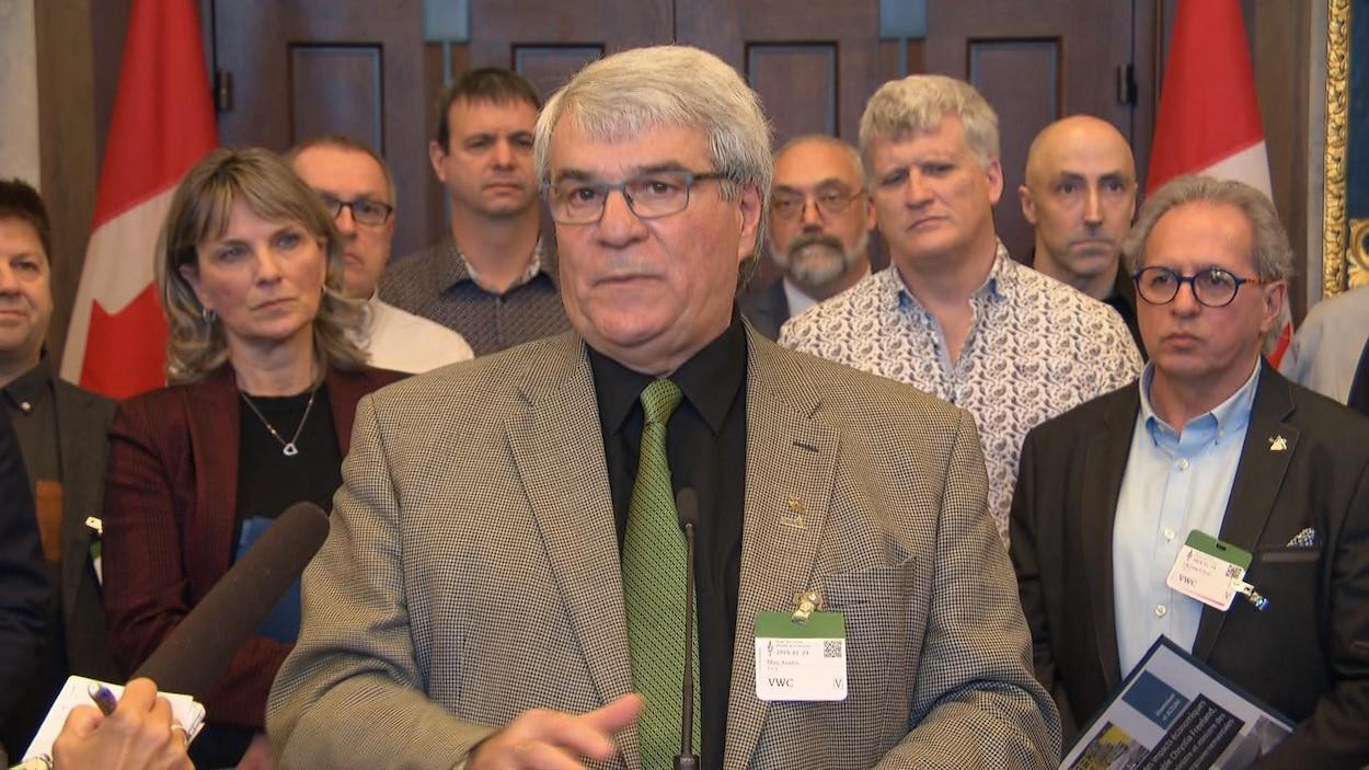Un groupe de personnes debout dans les couloirs du parlement canadien.