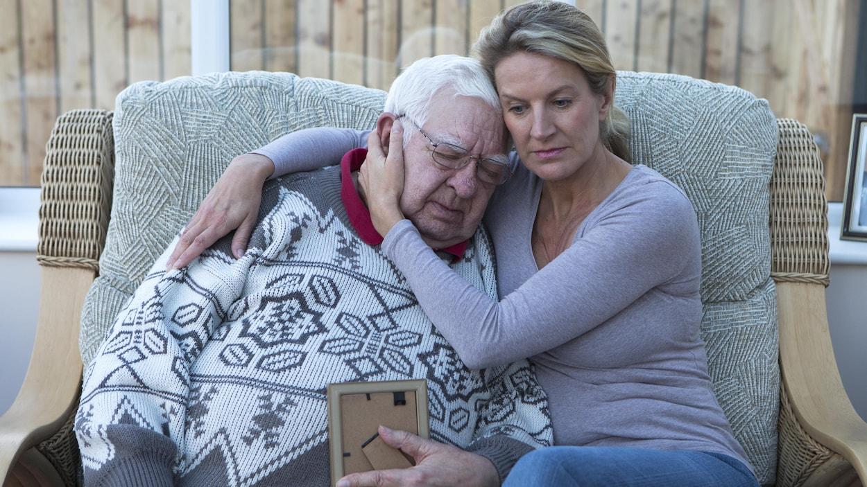 Un homme âgé assis sur le canapé avec sa fille, en regardant une photo.