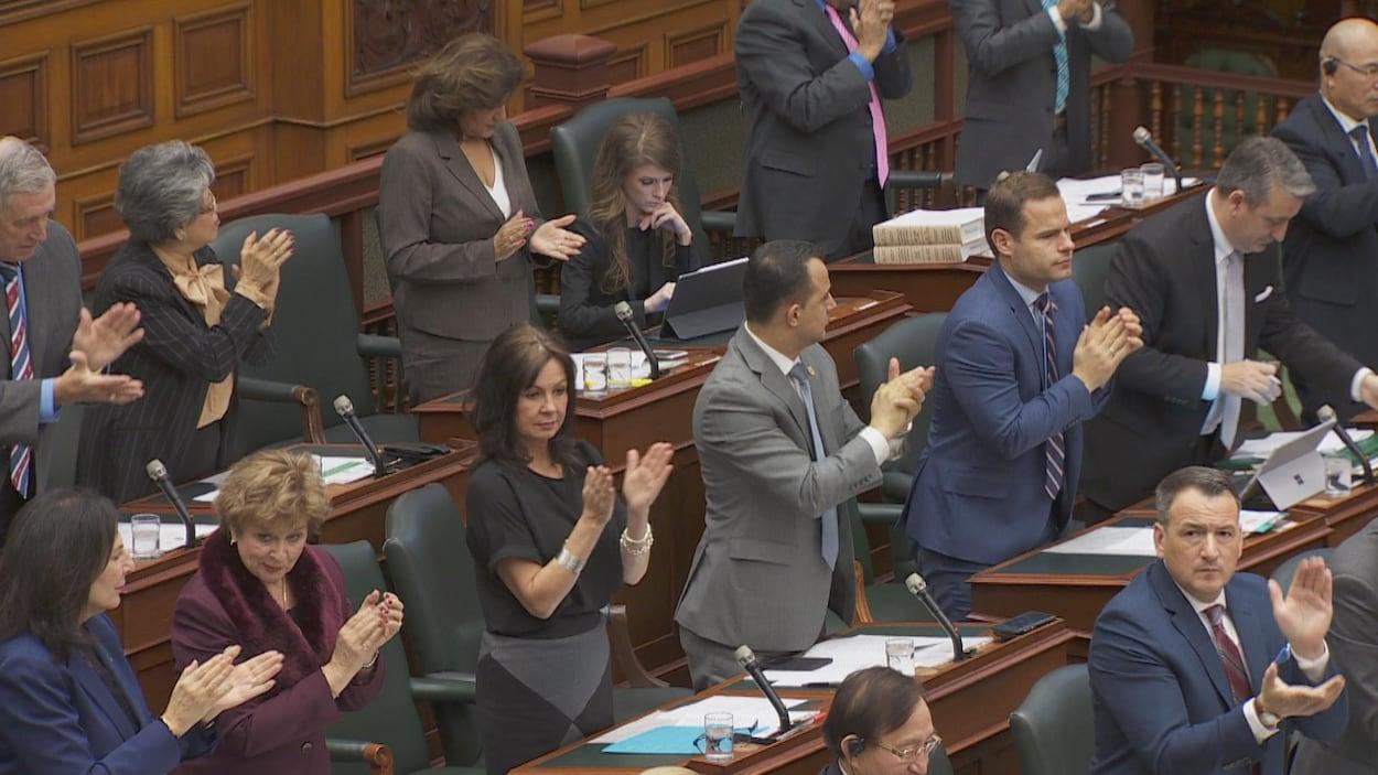 des hommes et des femmes debout en train d'applaudir à l'exception d'une femme assise fixant une tablette