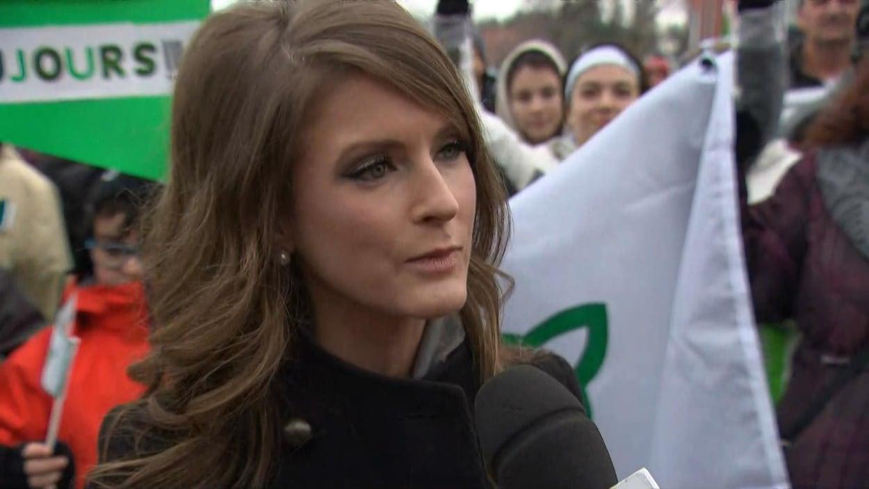 Amanda Simard répond aux questions d'une journaliste au milieu de la foule.