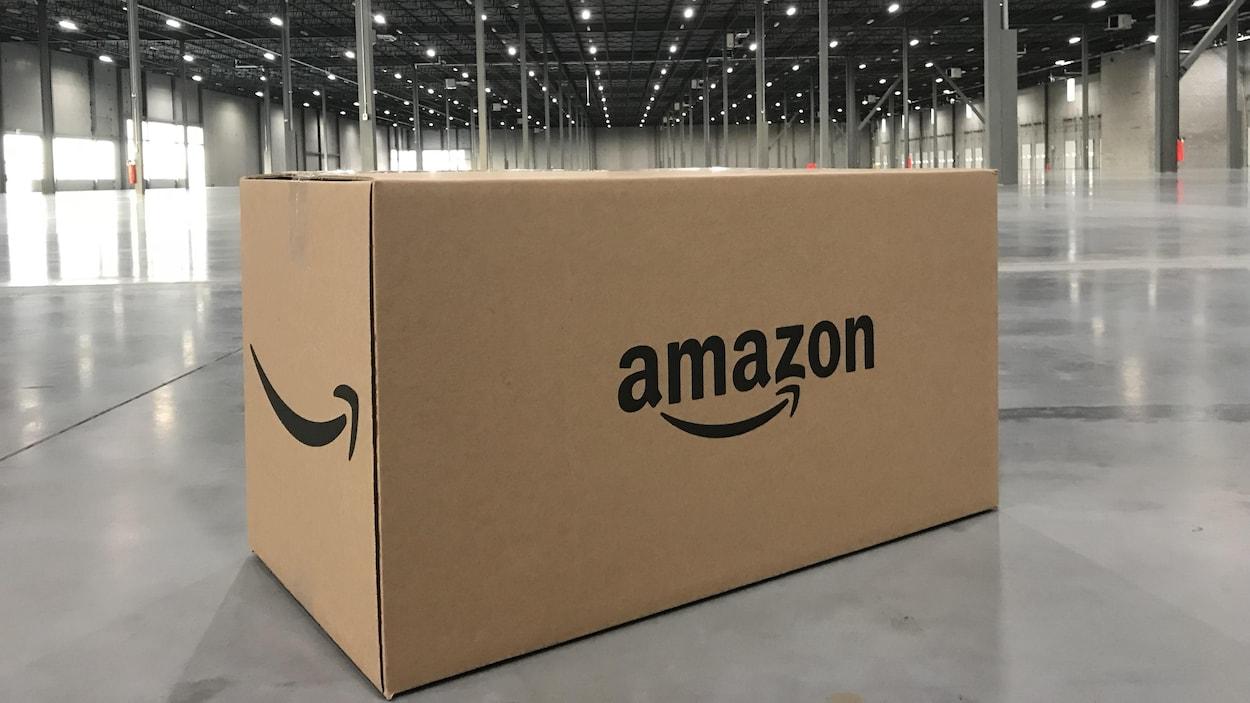 Une boîte portant le logo d'Amazon posée sur le sol d'un entrepôt vide.