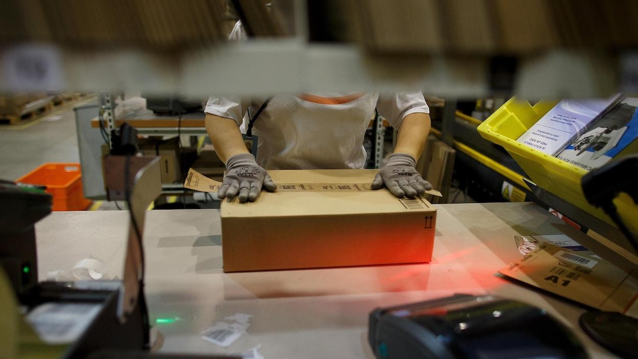 Une personne manipule une boîte de carton sur une table de travail.