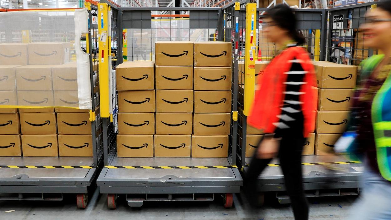 Une employée se promène à côté de boîtes dans un entrepôt d'Amazon.