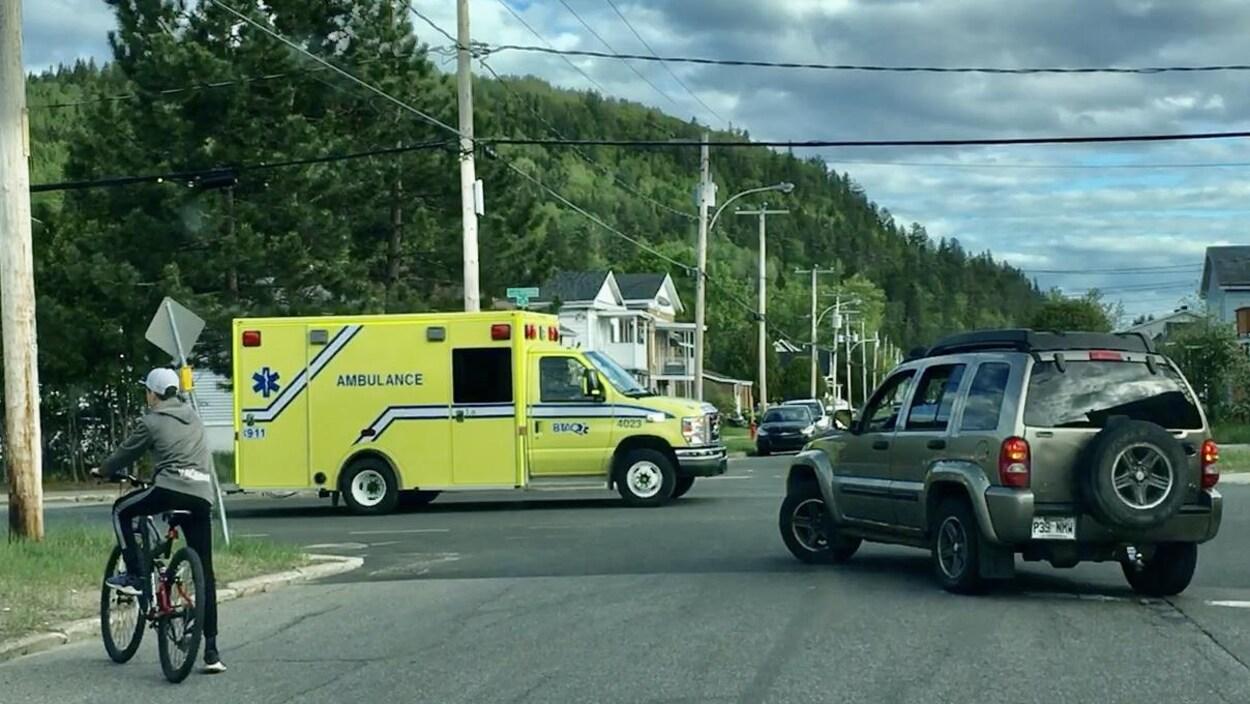 Une ambulance dans une rue qui bloque une voiture et des cyclistes.