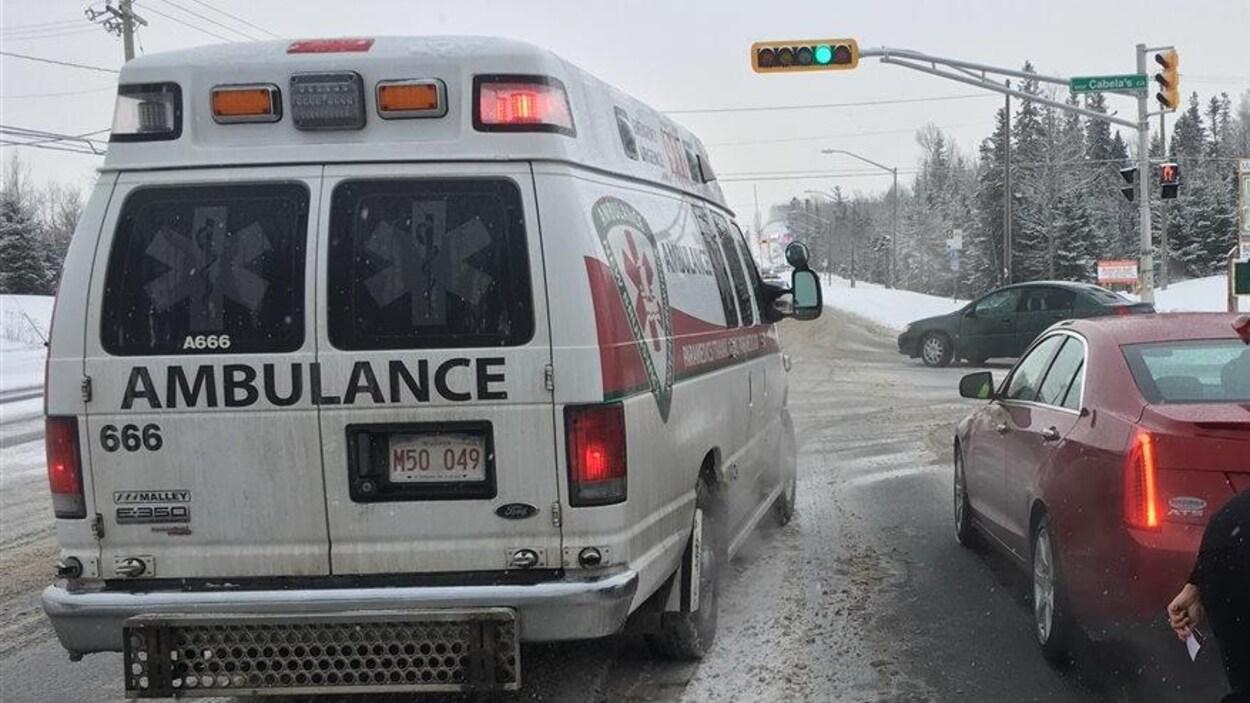 Une ambulance, en hiver, est arrêtée près d'une voiture rouge.