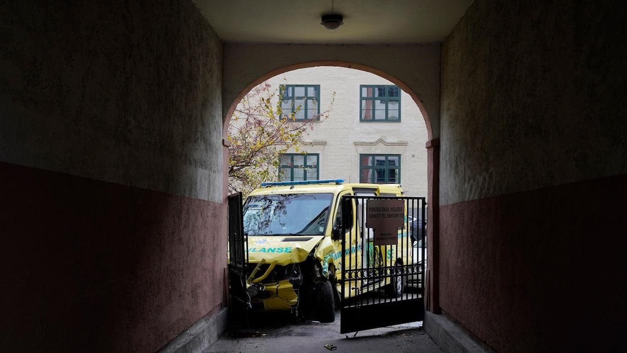 Une ambulance accidentée encombre une porte cochère.