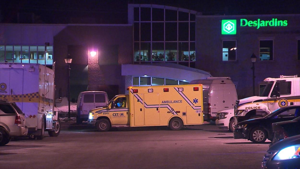 Dans le stationnement de la caisse Desjardins, on aperçoit des camions de la Sûreté du Québec et une ambulance.