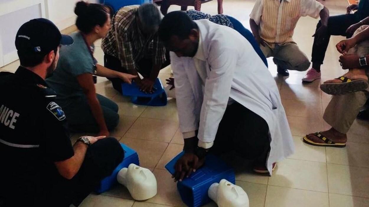 Des ambulanciers paramédicaux de l'Outaouais accroupis au sol pour donner de la formation dans un établissement du Djibouti.