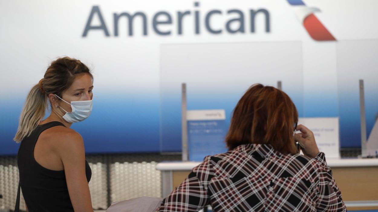 Deux femmes sont au guichet d'American Airlines,