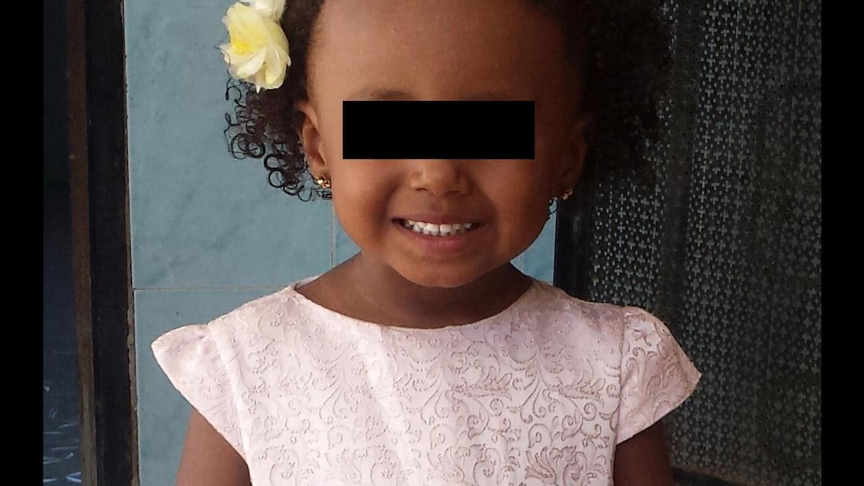 Amira avec une fleur dans les cheveux.