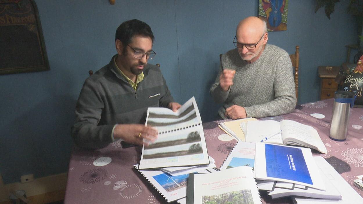Amit Virmani, de Naveco Power, et Daniel Brassard, montrent une étude sur les éoliennes dans la région.