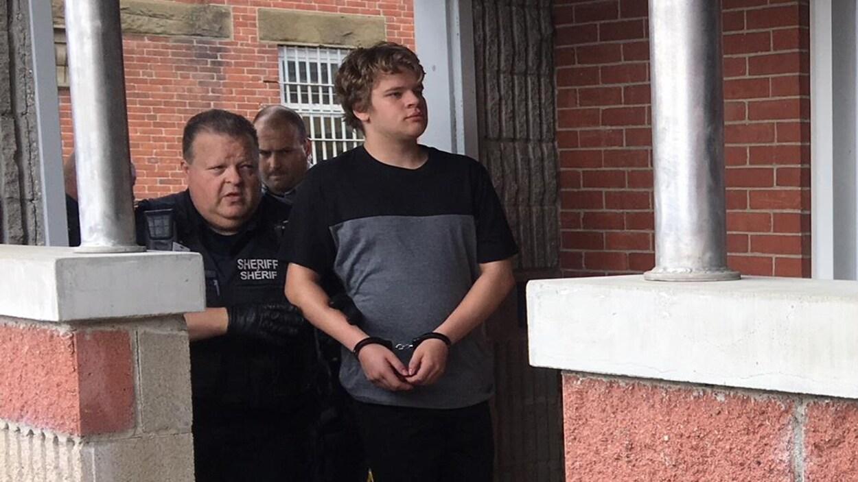 Amon Kelleter menotté accompagné de la police.