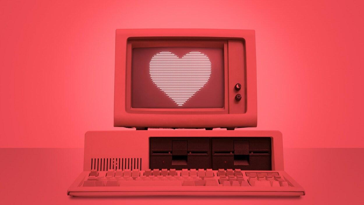 Une photo montrant un vieil ordinateur de bureau éclairé d'une lumière rouge dont l'écran affiche l'image d'un cœur.