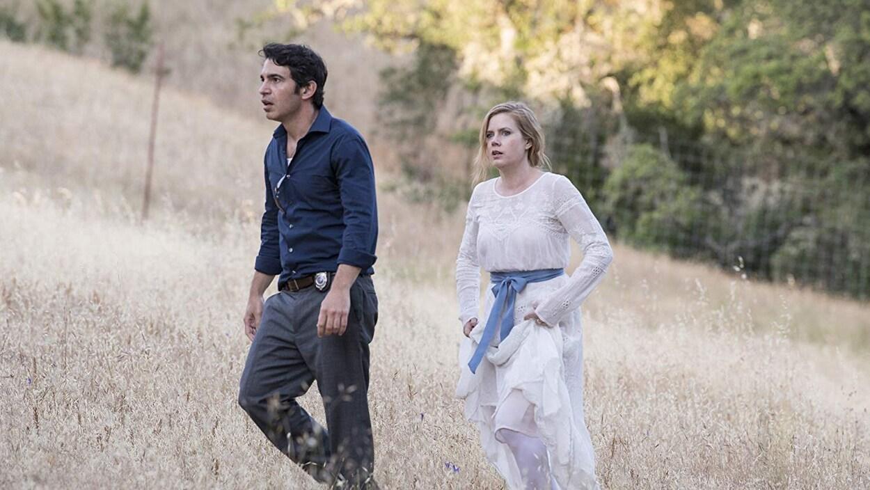 L'air inquiet, Amy Adams et Chris Messina marchent dans un champ dans une scène de la minisérie «Sharp Objects».