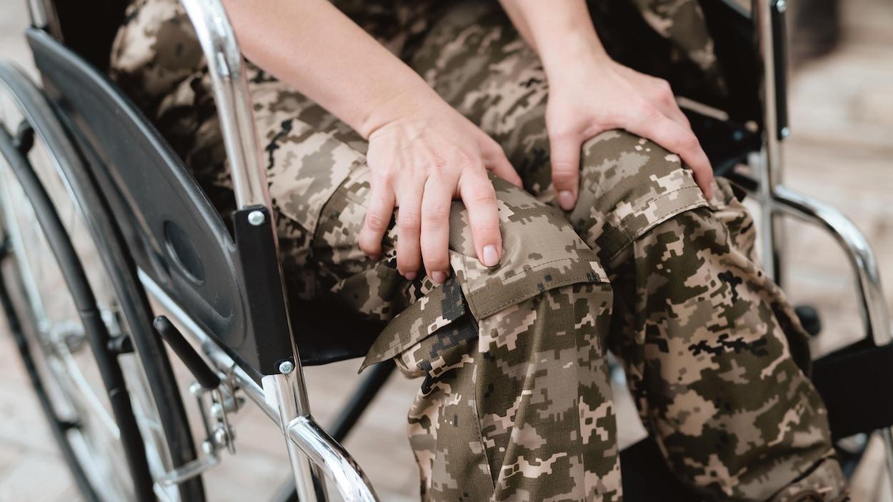 Une femme vêtue d'habits de camouflage installée dans une chaise roulante.