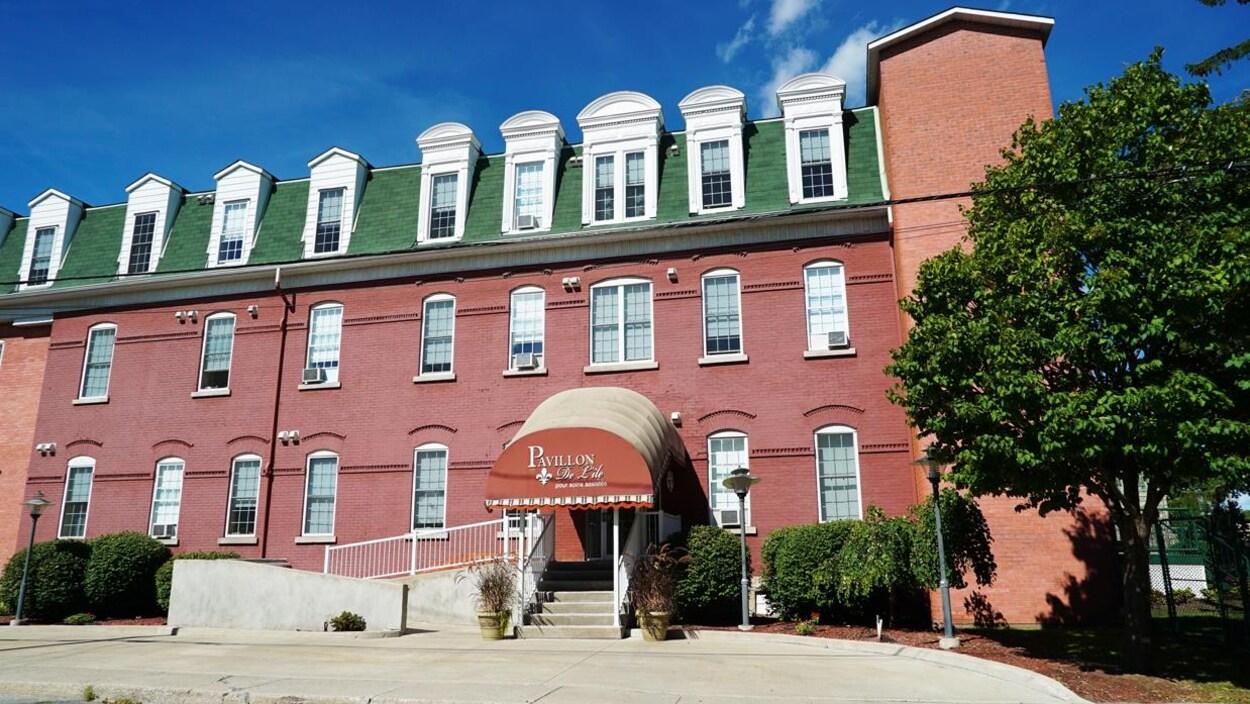 L'édifice de trois étages, au toit vert, est en brique rose