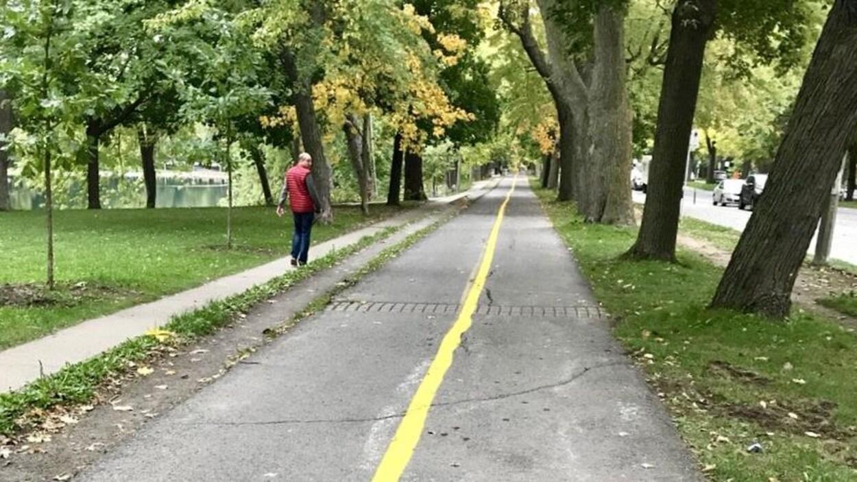Un homme marche sur un sentier qui longe la piste cyclable.