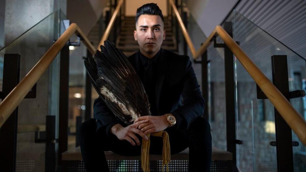 Un jeune homme, Andre Bear, est assis dans un escalier. Il est entièrement vêtu de noir et tient dune parure autochtone de plumes d'oiseaux dans ses mains.