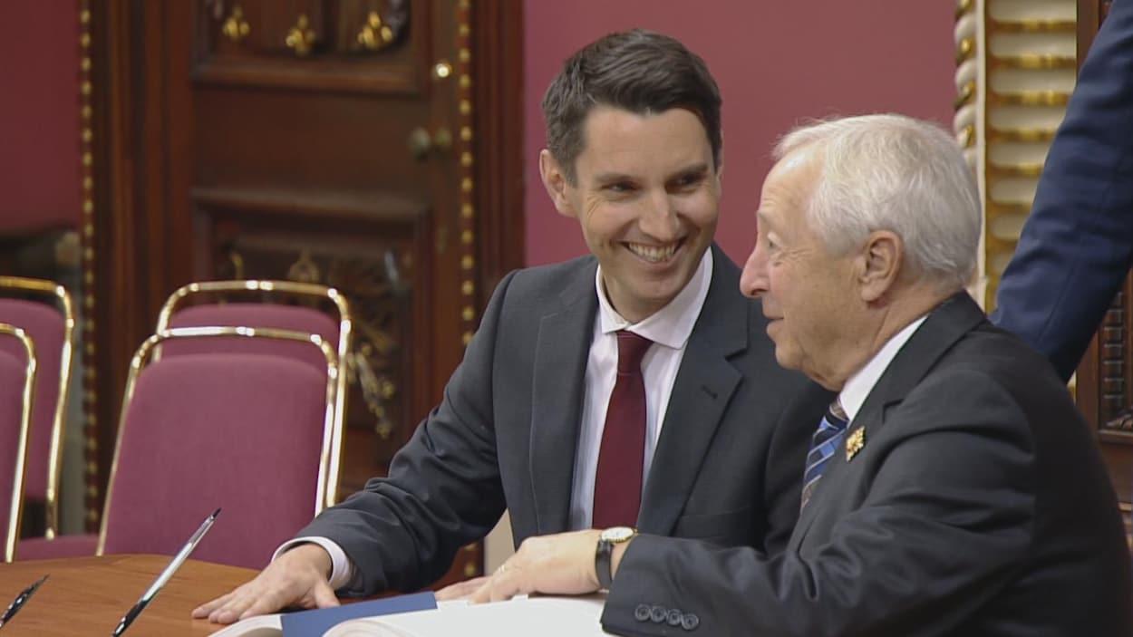 Tout sourire, André Fortin vient de signer le registre des serments du Conseil exécutif  aux côtés du lieutenant-gouverneur Michel Doyon.