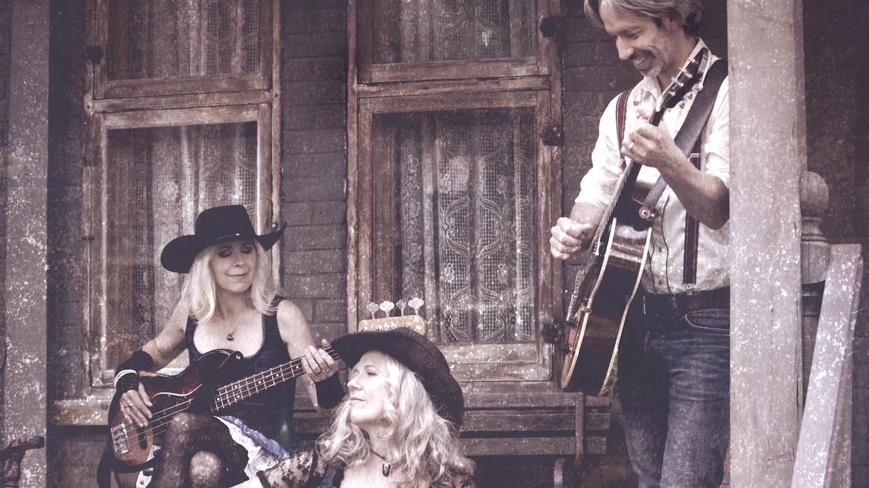André Lavergne, Annette et Michelle Campagne jouent de la guitare sur le porche d'une maison.