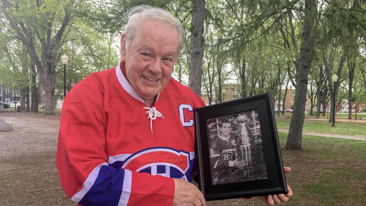 André Pronovost tient dans ses mains une photo en noir et blanc de Maurice Richard et la Coupe Stanley.