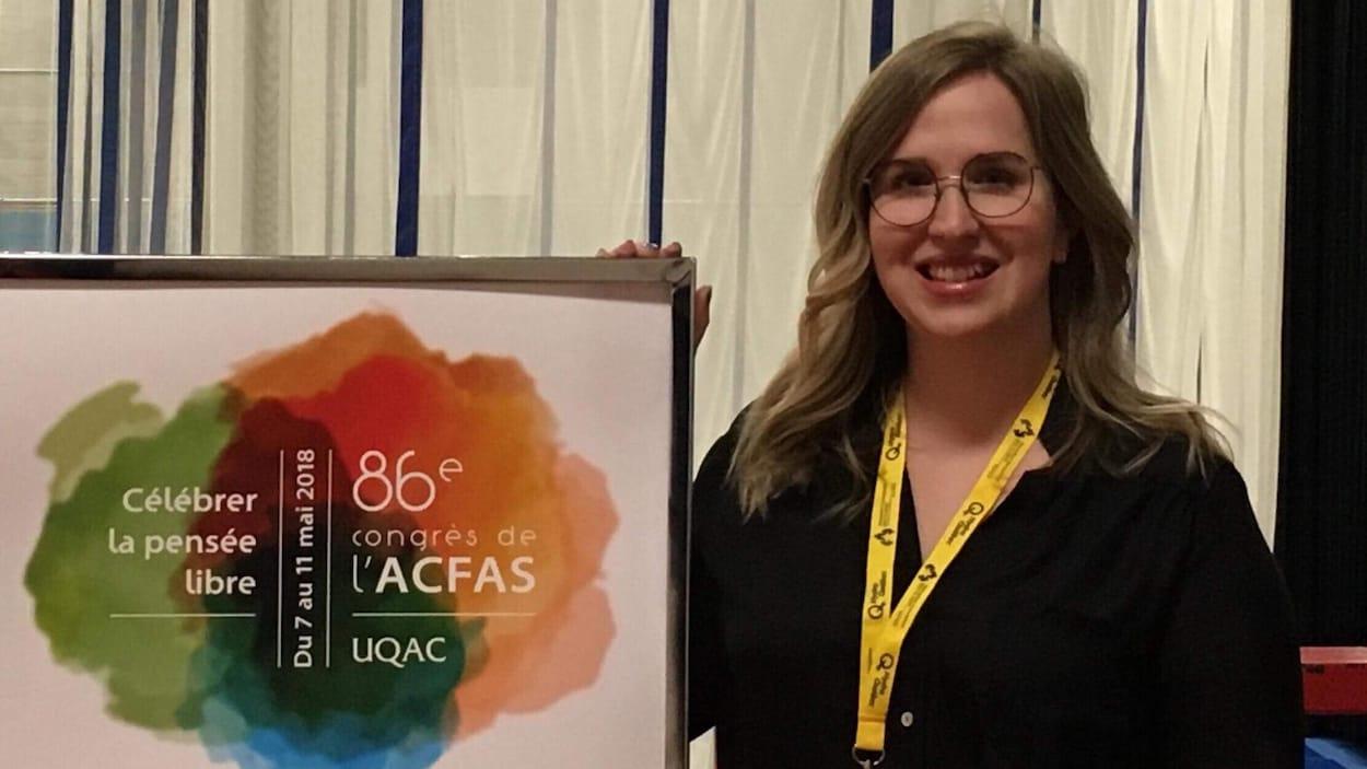 Photo d'Andrée-Anne Lefebvre à côté d'une affiche du congrès.