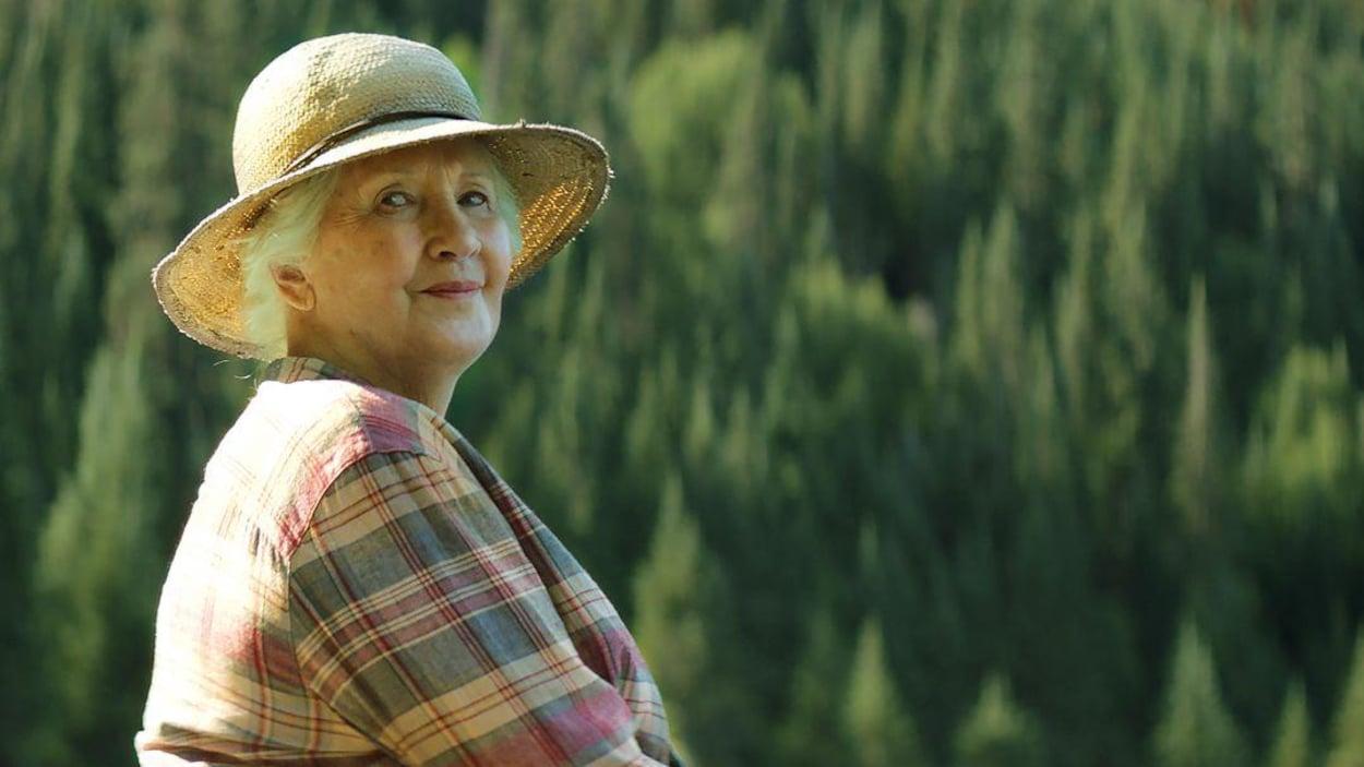 La comédienne Andrée Lachapelle en forêt dans une scène du film Il pleuvait des oiseaux. Elle porte un chapeau de paille et une chemise légère.