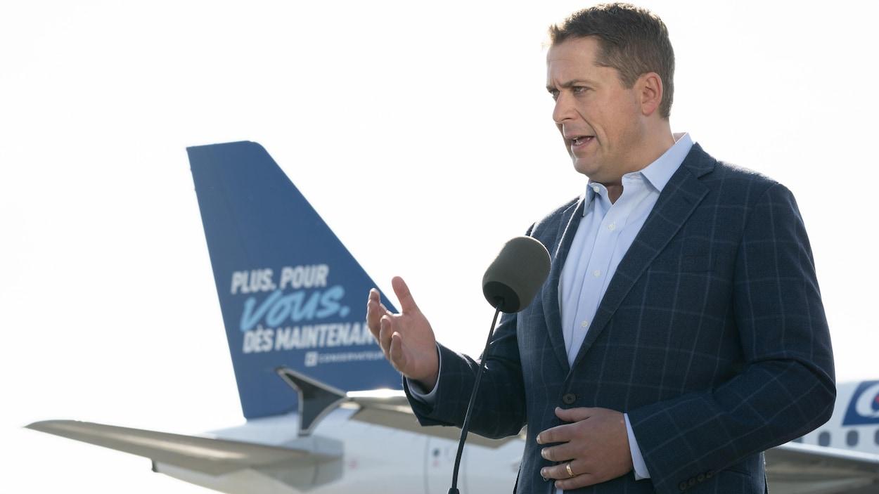 Andrew Scheer, devant la queue d'un avion sur laquelle on peut lire le slogan du Parti conservateur.