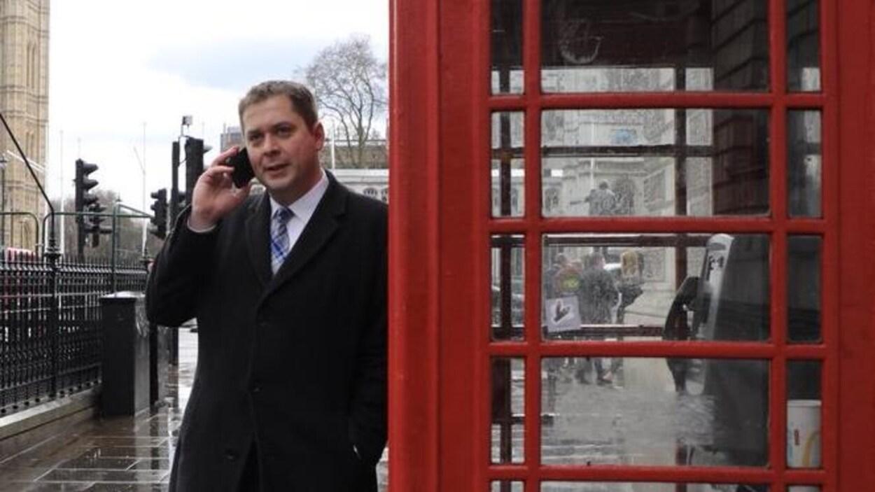 Andrew Scheer parle au cellulaire adossé à une cabine téléphonique rouge à Londres.
