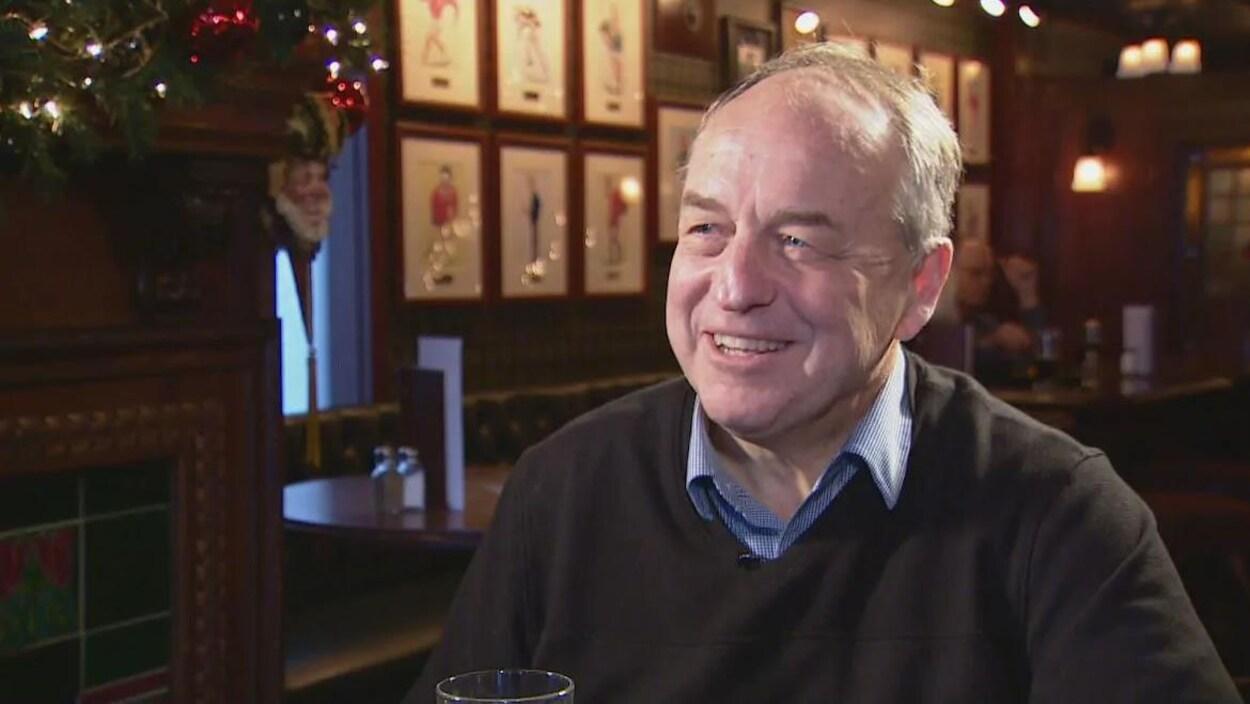 Andrew Weaver sourit en tenant un verre. En arrière-plan, des décorations au mur et la banquette d'un pub.