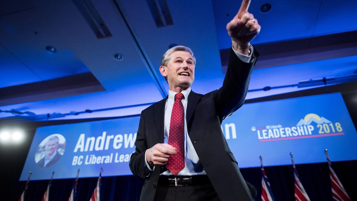 Andrew Wilkinson debout sur scène pointe son doigt vers la foule alors qu'en arrière-plan se trouvent des drapeaux de la Colombie-Britannique et son affiche de campagne à la direction du parti.