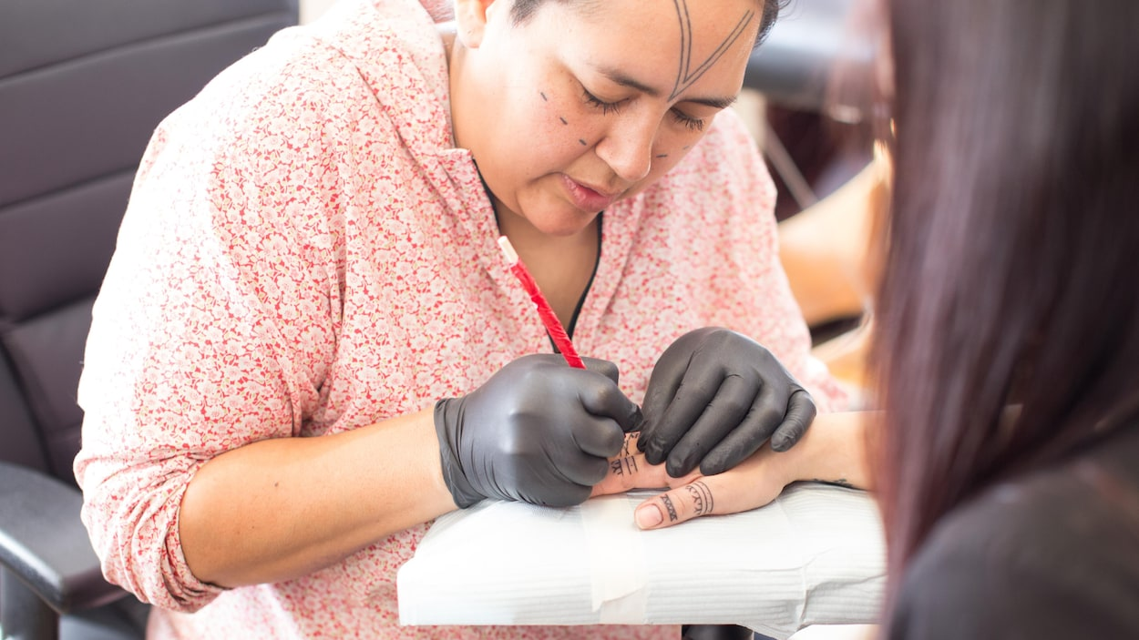 Angela Hovak Johnston tatouant la main d'une femme inuite selon la technique traditionnelle