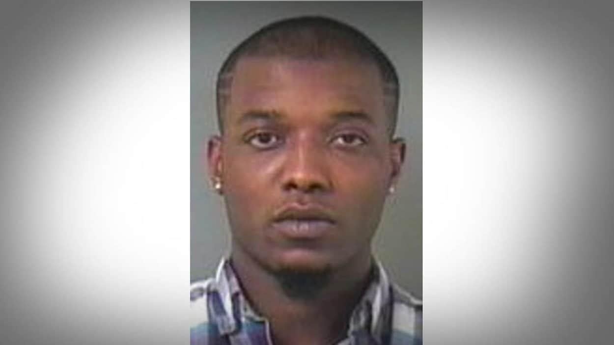 Le portrait d'un homme noir à la tête rasée, portant des boucles d'oreilles et vêtu d'une chemise à carreaux.