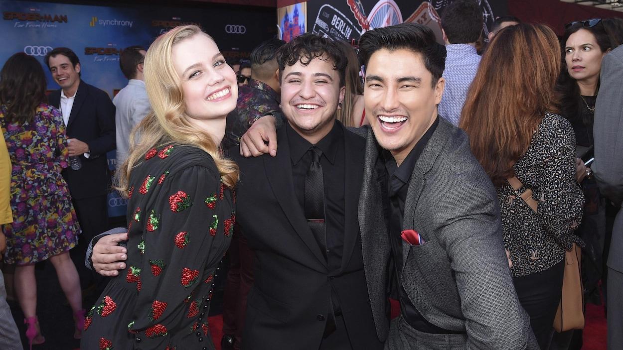 Les trois acteurs sourient pour la photo.