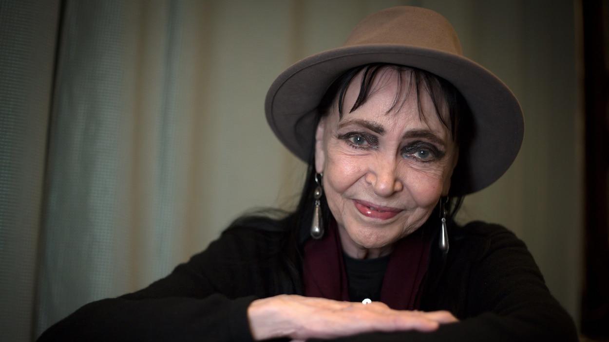 Une femme souriante, aux yeux bleus, porte un chapeau.