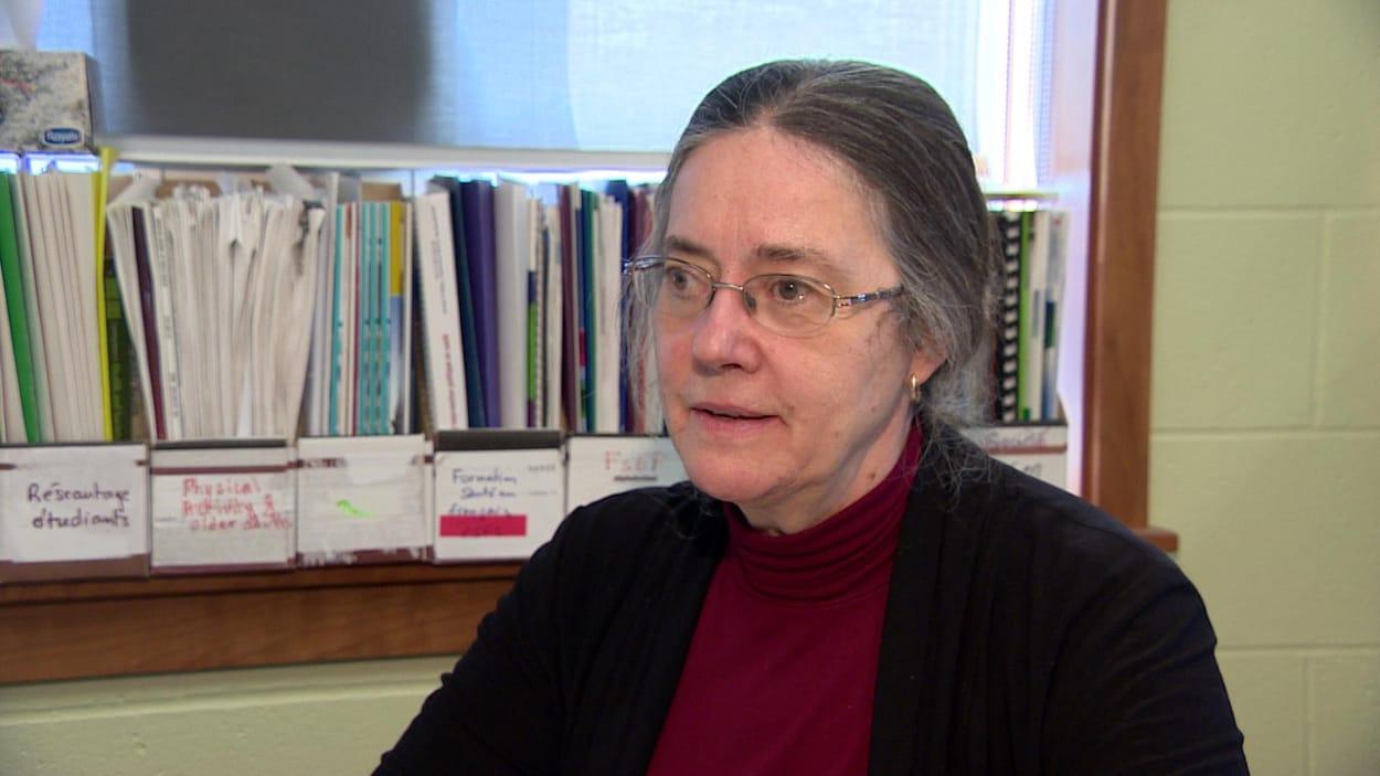 Une femme aux cheveux grisonnants et portant des lunettes de vue.