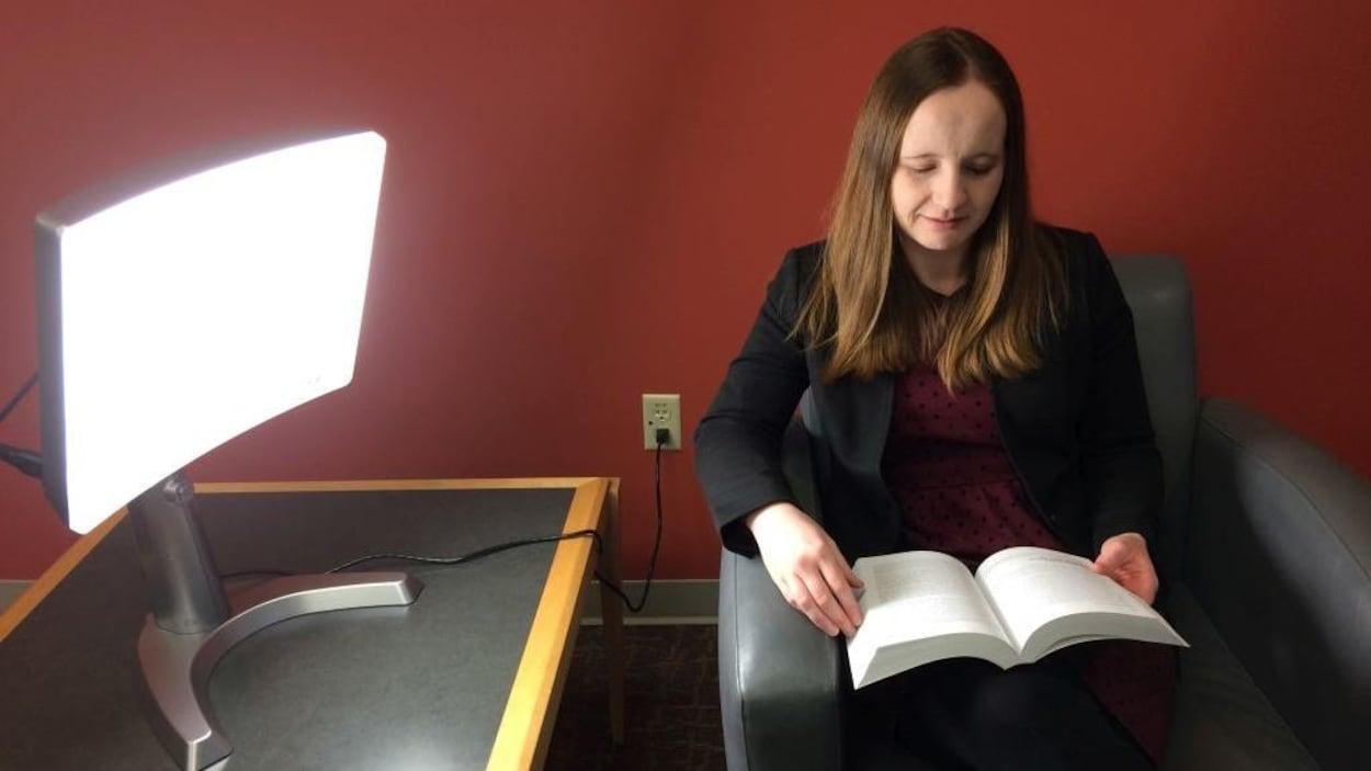 La directrice des services aux consommateurs à la bibliothèque municipale de London, Anne O'Sullivan lit au chevet d'une lampe de luminothérapie.