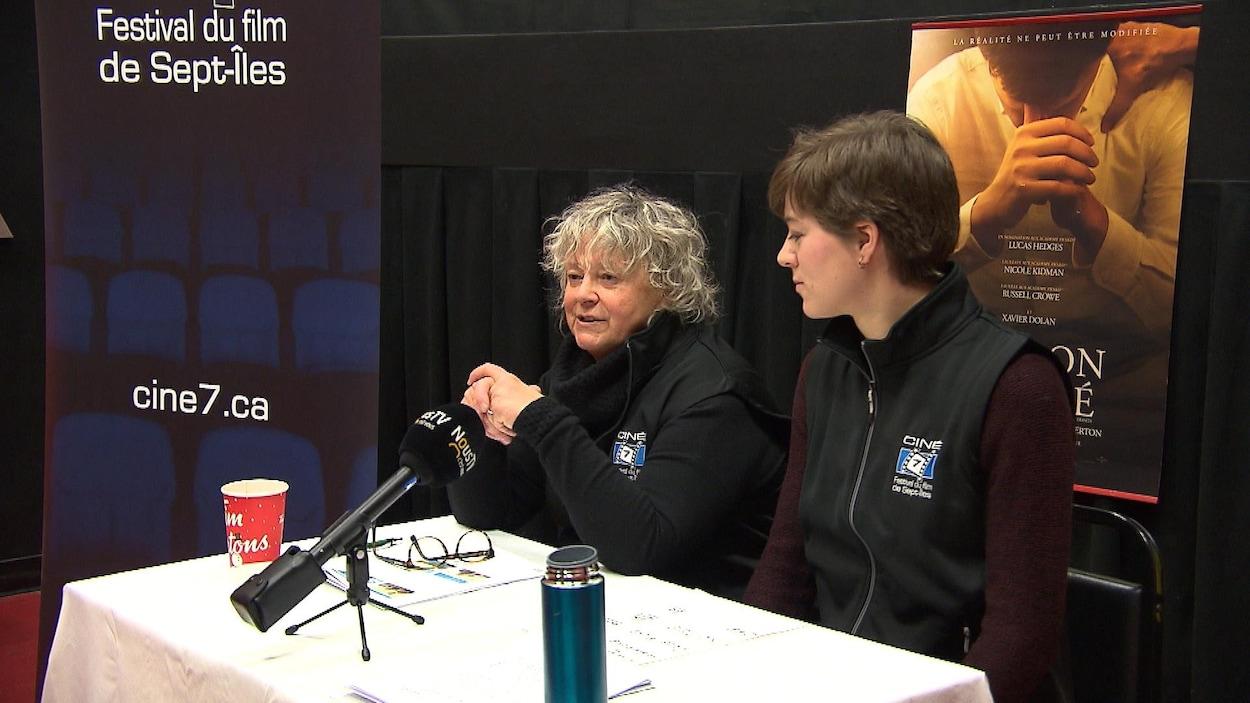 Deux femmes parlent au micro dans une conférence de presse.