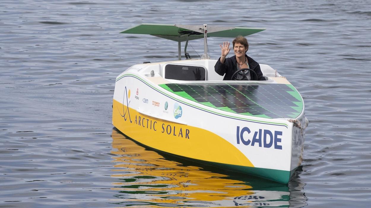 Une femme fait un signe de la main alors qu'elle est à la barre d'un petit bateau, nommé Icade, sans voile, ne fonctionnant qu'à l'énergie solaire. Des panneaux solaires recouvrent tout l'avant du bateau.