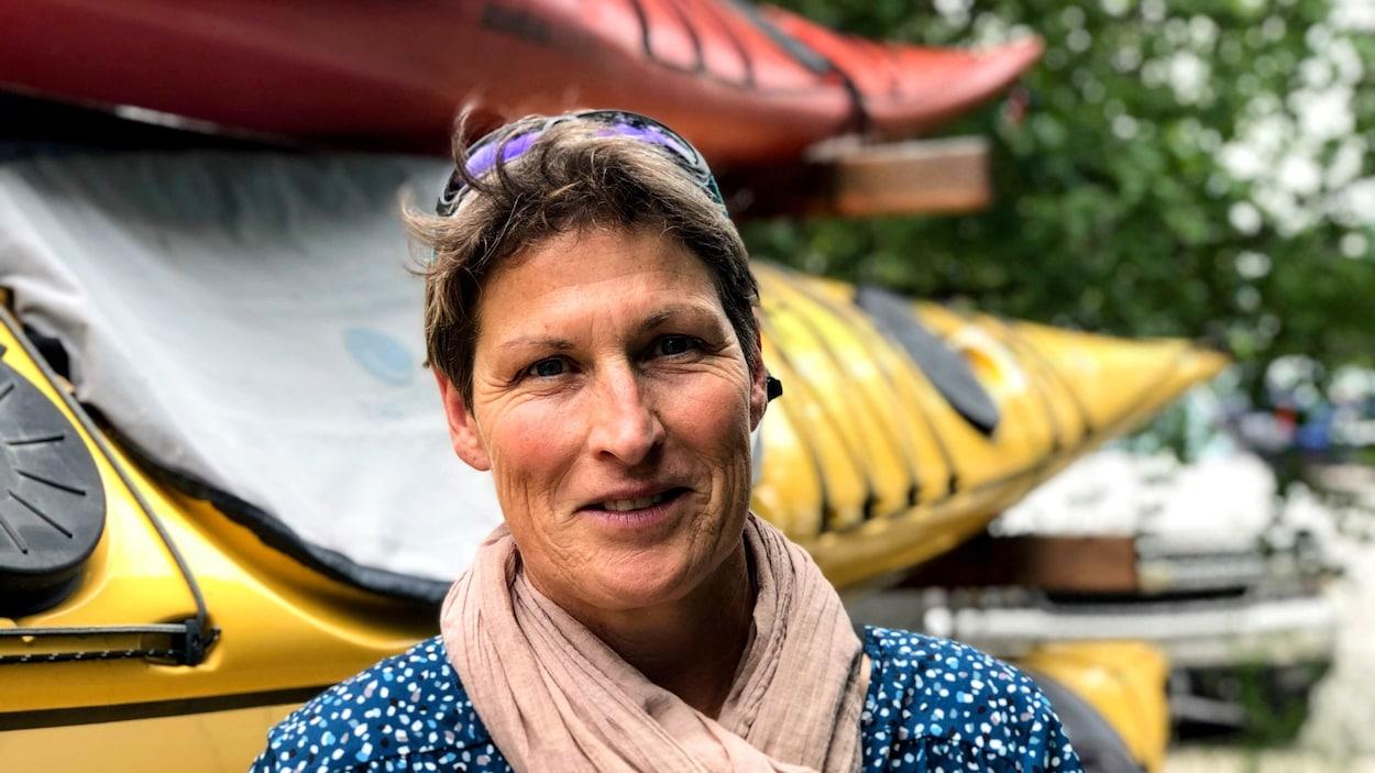 Une femme devant des kayaks.