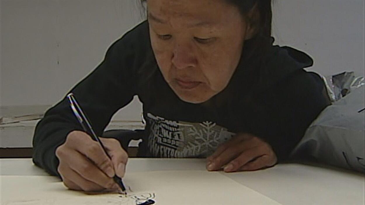 Annie Pootoogook est en train de dessiner avec un crayon noir sur une feuille blanche.