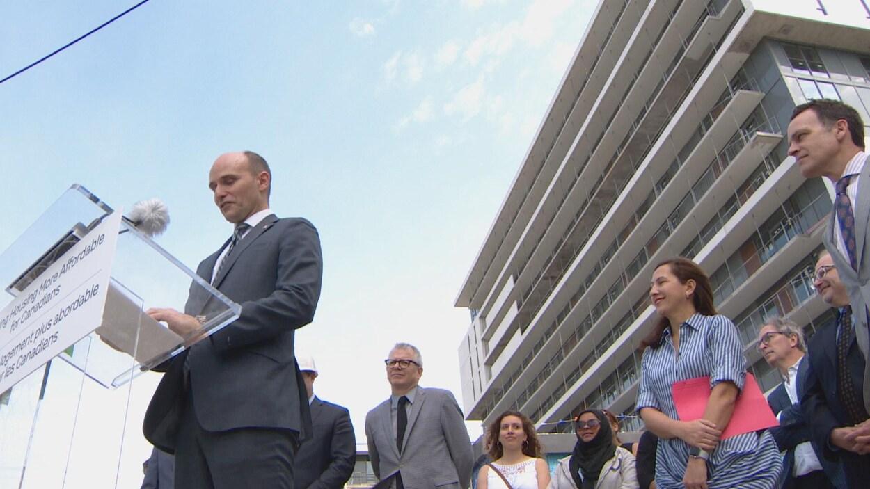Jean-Yves Duclos fait une annonce dehors sur un chantier de construction, accompagné de membres du gouvernement
