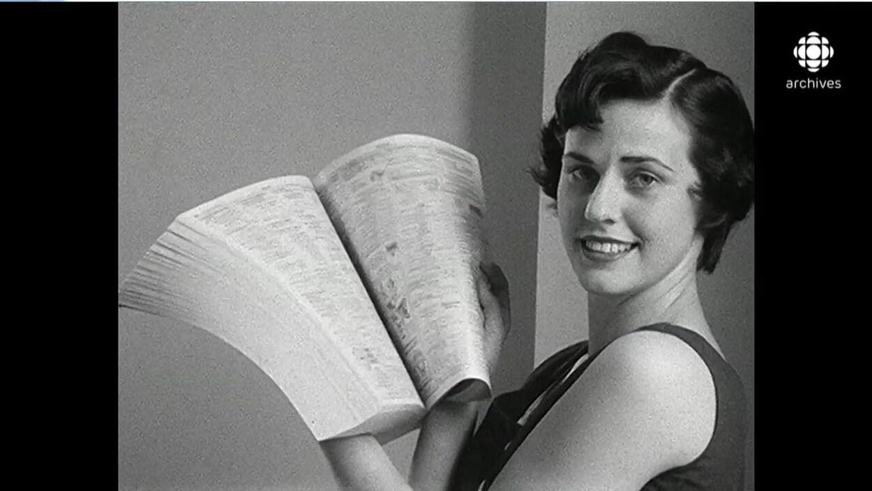 En noir et blanc, femme tout sourire posant avec un bottin téléphoniques ouvert entre ses mains,
