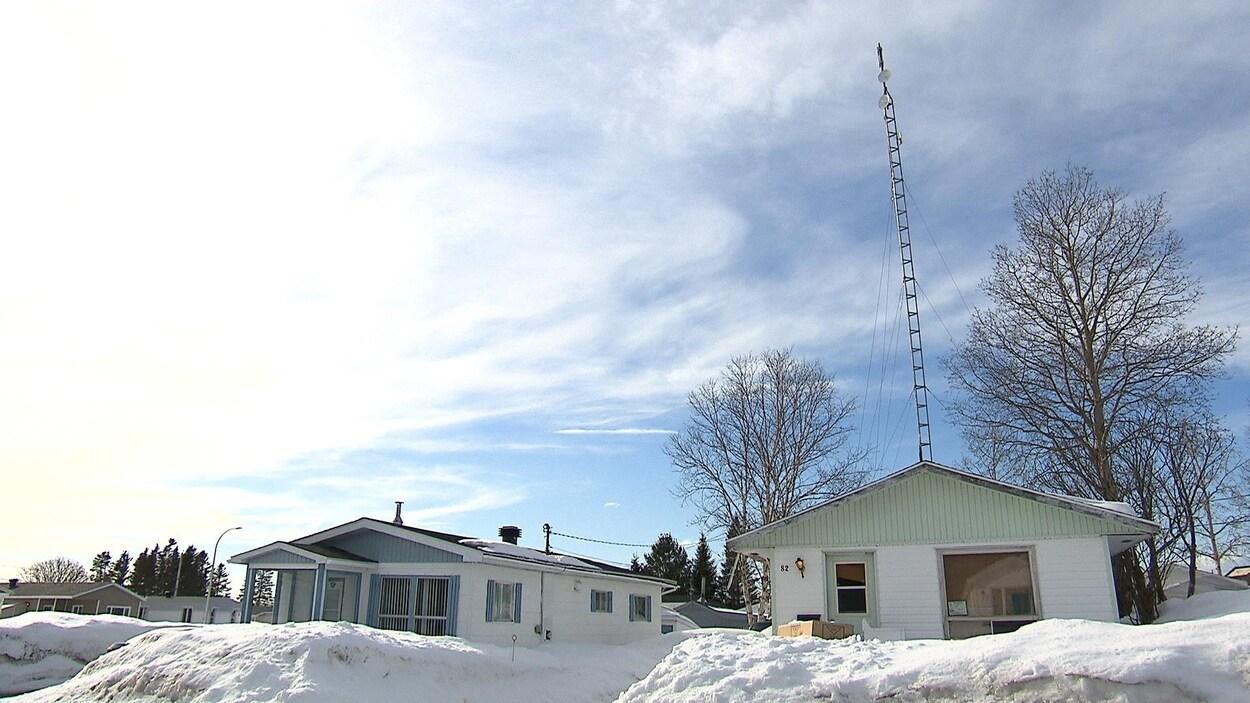 Deux maisons dans un décor très enneigé. De l'une d'elles s'élève une haute et mince tour de télécommunications.