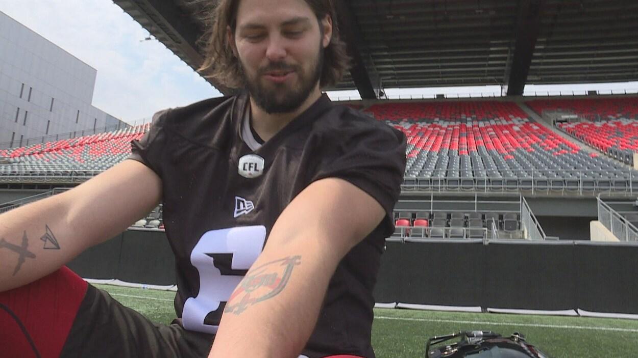 Un joueur de football assis sur le terrain dans un stade