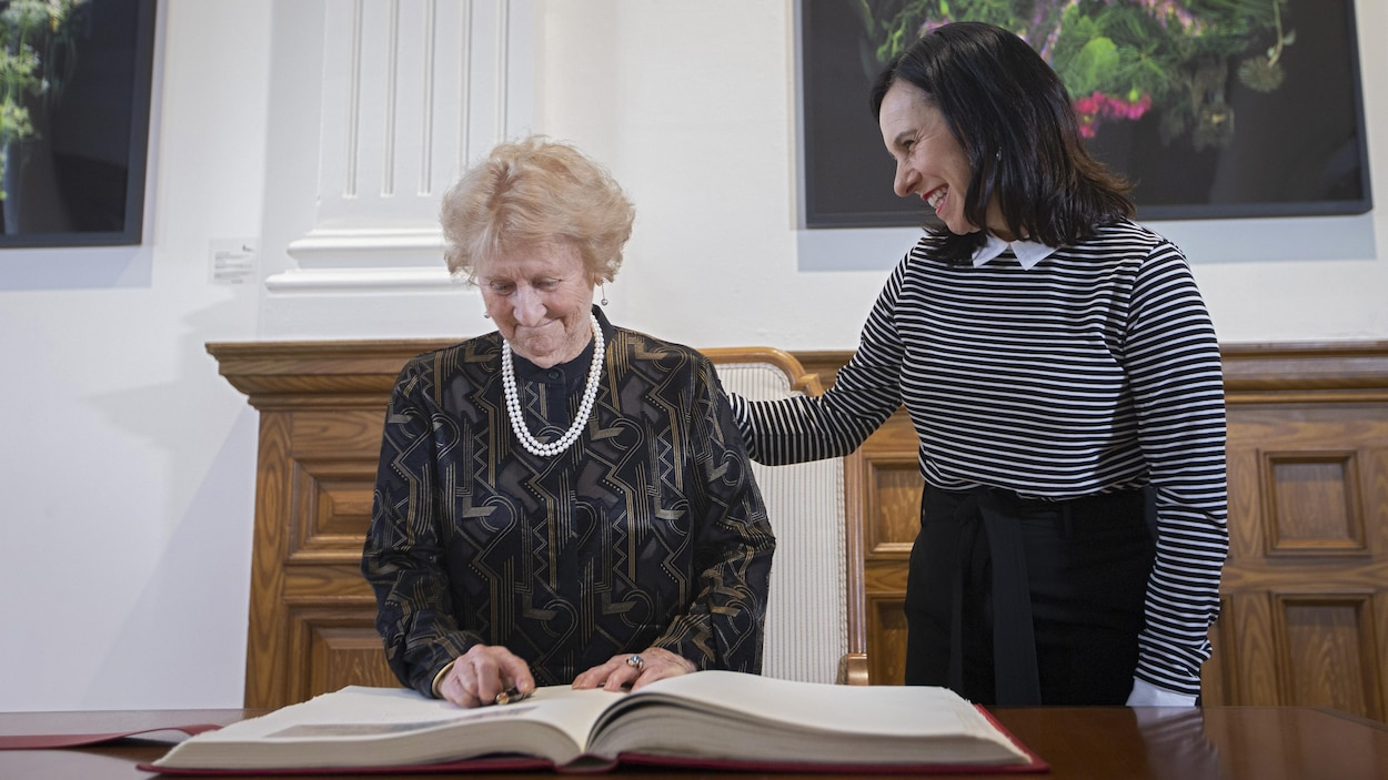 Antonine Maillet devant le livre d'or de la Ville de Montréal, avec à ses côtés Valérie Plante.