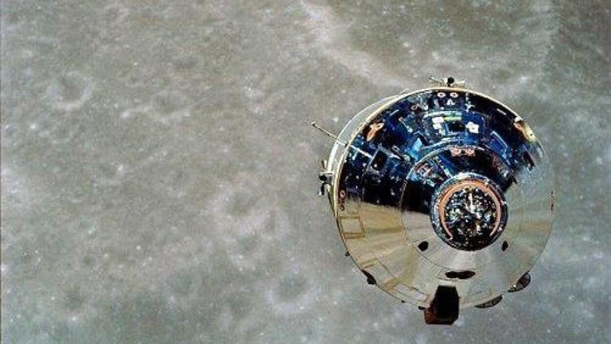 Un objet métallique flotte dans l'espace, en direction de la surface de la lune.