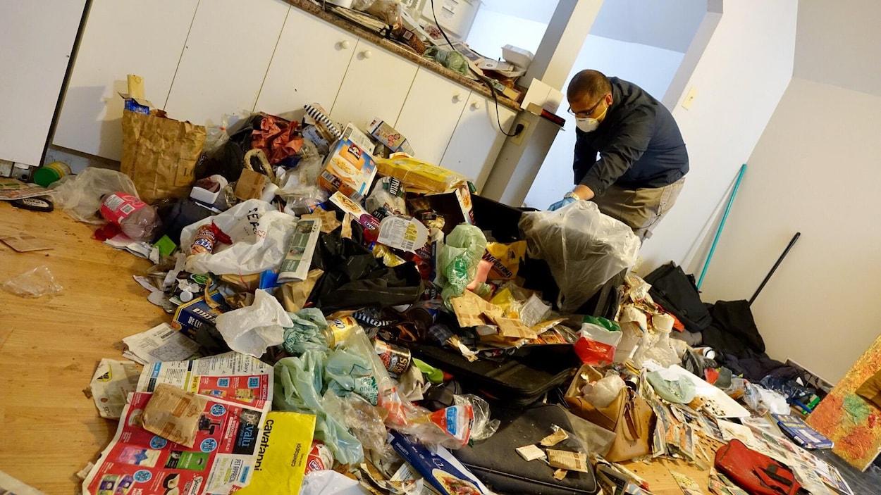 Portant un masque, le propriétaire du logement nettoie l'appartement recouvert d'une imposante quantité de déchets de toute sorte.