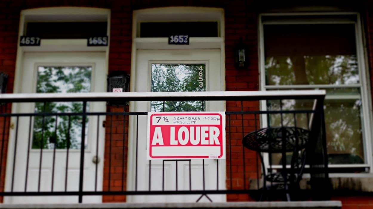 Un immeuble d'appartements à Montréal avec une pancarte « À louer » devant l'une de ses portes.