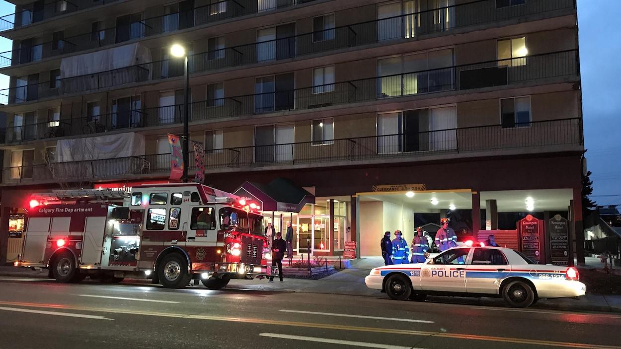 Un camion de pompiers et une voiture de police devant un immeuble d'appartements.